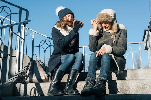 Le ragazze adolescenti gridano nella tazza di carta del megafono