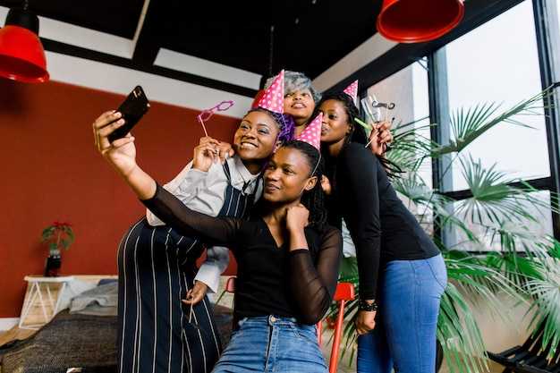 Le ragazze africane felici celebrano il compleanno in cappelli e scattano foto su uno smartphone
