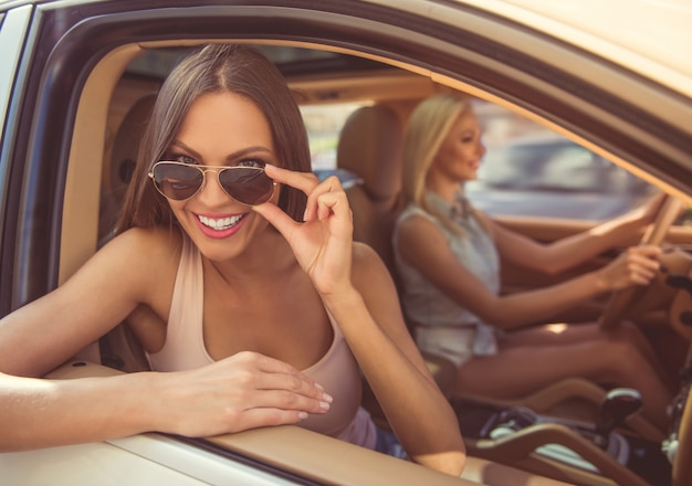 Le ragazze alla moda sorridono e si divertono mentre guidano l'auto.