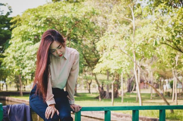 Le ragazze asiatiche che indossano abiti sono sedute tristi, senza lavoro. perché essere risolto dalla società
