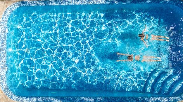 Le ragazze attive nella vista aerea del drone dell'acqua della piscina da sopra, i bambini nuotano, i bambini si divertono sulla vacanza di famiglia tropicale, concetto del centro di villeggiatura