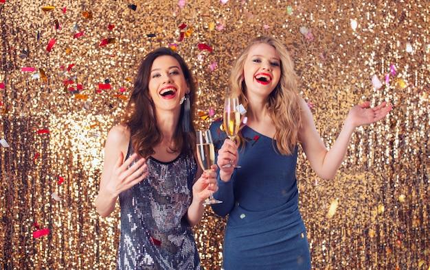 Le ragazze bevono spumante per festeggiare il nuovo anno