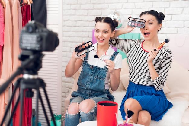 Le ragazze blogger reggono i pennelli e gli ombretti.