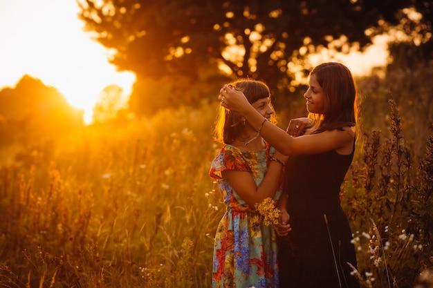 Le ragazze calme stanno sul campo della sera