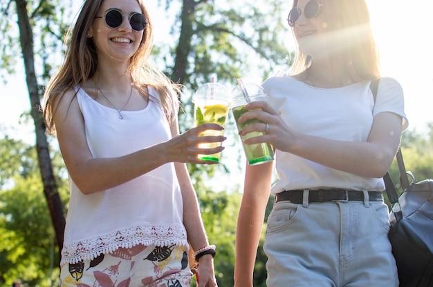 Le ragazze camminano nel parco e bevono il mojito
