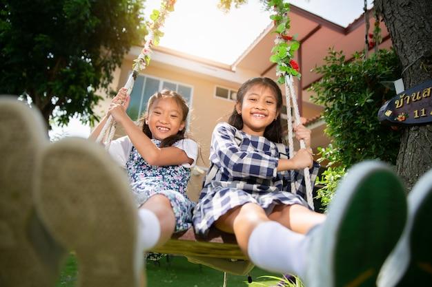 Le ragazze carine adorano giocare a swing insieme