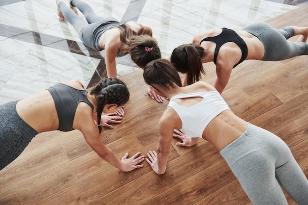 Le ragazze che fanno push up insieme. testa vicino testa posa sul pavimento in legno e piastrelle
