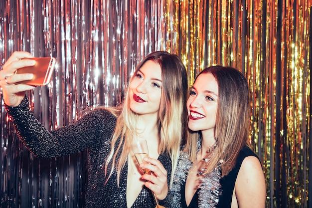 Le ragazze che prendono selfie su partiti di nuovi anni