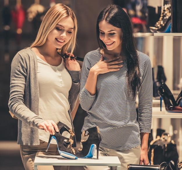 Le ragazze con le borse della spesa stanno scegliendo le scarpe e stanno sorridendo