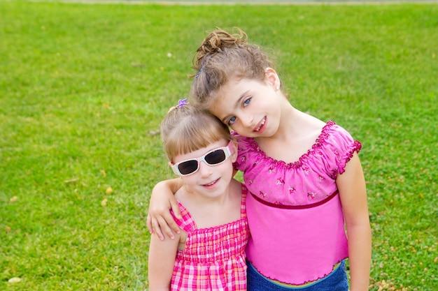 Le ragazze dei bambini si abbracciano nel parco dell'erba verde
