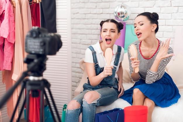 Le ragazze del blogger reggono i pettini cantando alla telecamera.