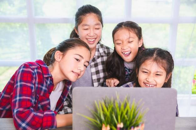Le ragazze dell'allievo godono lo studio e l'apprendimento dal pc del computer portatile, di nuovo al concetto della scuola