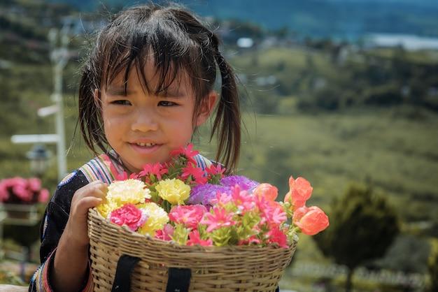 Le ragazze della tribù hmong tengono il suo cesto di bambù con fiori