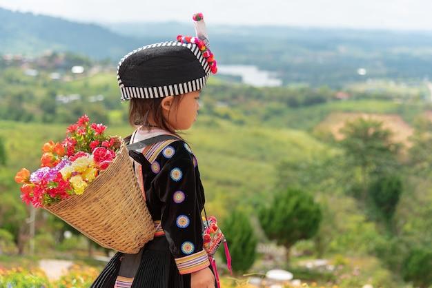 Le ragazze della tribù hmong trattengono il suo cesto di fiori di bambù