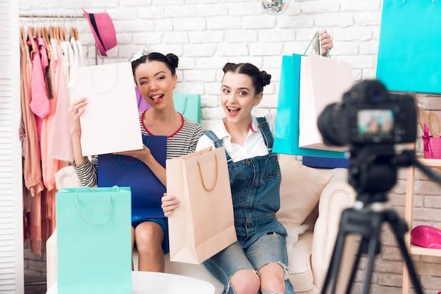 Le ragazze di blogger presentano borse colorate per la fotocamera.