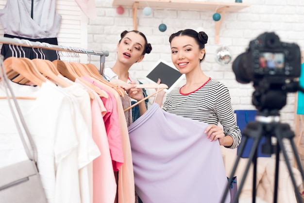 Le ragazze di blogger presentano un abito colorato alla fotocamera.