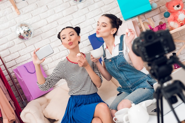 Le ragazze di moda blogger bevono tè alla telecamera.