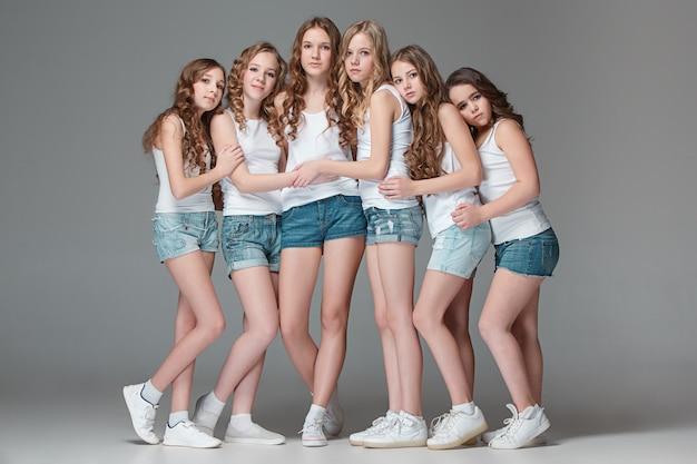 Le ragazze di moda che stanno insieme e che esaminano macchina fotografica sopra il fondo grigio dello studio
