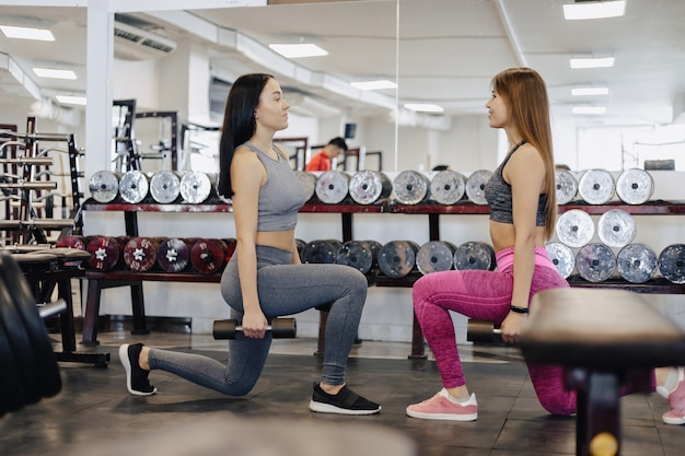 Le ragazze fanno i manubri in palestra, fitness