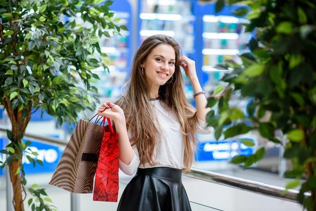 Le ragazze felici fanno shopping al centro commerciale.