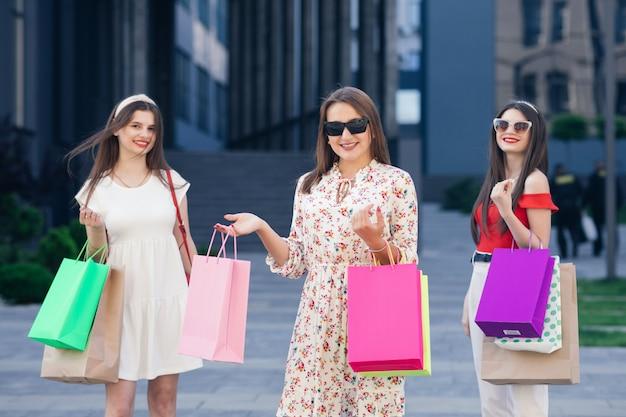 Le ragazze ricche facevano la spesa. donne sorridenti felici con i sacchetti che camminano sulla strada.