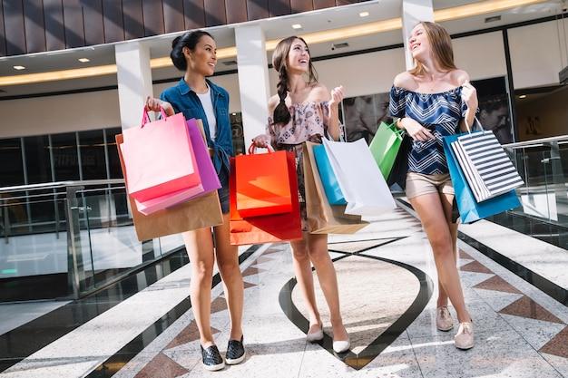 Le ragazze ridendo camminano nel centro commerciale