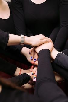 Le ragazze si mettono le mani l'una sull'altra. le persone uniscono le mani. concetto di cooperazione di lavoro di squadra di supporto di gruppo.