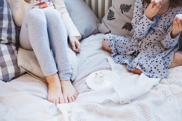 Le ragazze si siedono sul letto e mangiano prelibatezze natalizie