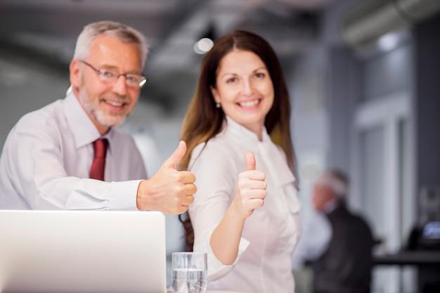 Le riuscite persone di affari sorridenti che mostrano il pollice su firmano dentro l'ufficio