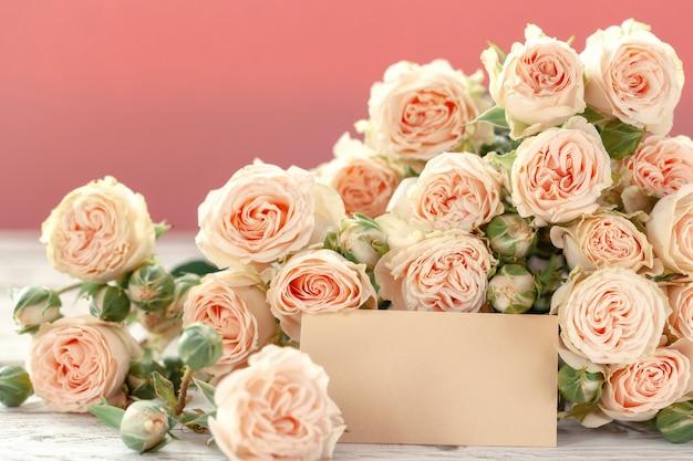 Le rose rosa fiorisce con un gallo per testo su fondo rosa. festa della mamma, compleanno, san valentino, concetto di giorno della donna.
