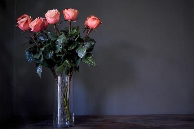 Le rose rosa fioriscono il mazzo in un chiaro vaso di cristallo alto contro una parete grigia, fuoco selettivo