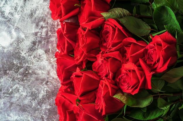 Le rose rosse luminose con le foglie verdi si trovano su un fondo scuro.