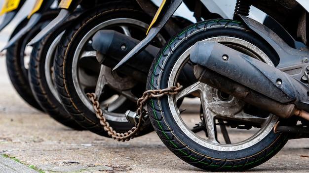 Le ruote posteriori della catena dello scooter per la consegna della pizza sono bloccate con una catena antifurto
