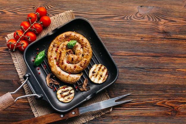 Le salsiccie grigliate deliziose a spirale con le verdure affettano in pentola su superficie di legno