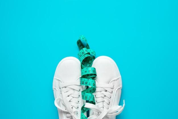 Le scarpe da ginnastica sono legate con misurazione su sfondo blu. il concetto di uno stile di vita attivo, la disposizione dell'appartamento. promozione di camminare e una perdita di peso bonus. vista dall'alto.