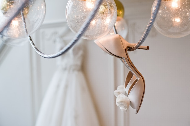 Le scarpe da sposa pendono sul lampadario all'interno di un hotel di lusso
