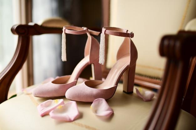 Le scarpe da sposa rosa stanno su una sedia con petali di rosa rosa