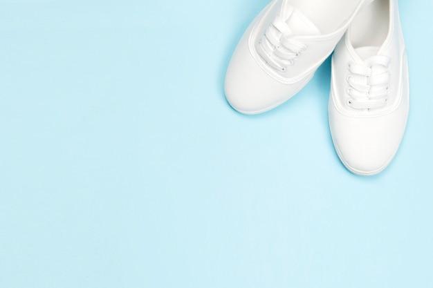 Le scarpe da tennis delle belle donne bianche su un fondo blu, copiano lo spazio, negozio di scarpe di concetto
