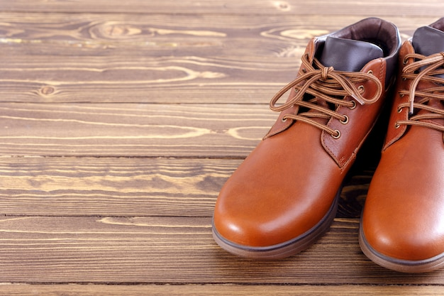 Le scarpe degli uomini alla moda su un fondo di legno con lo spazio della copia.