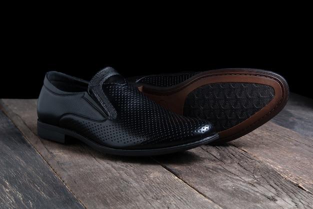 Le scarpe degli uomini neri sulla tavola di legno