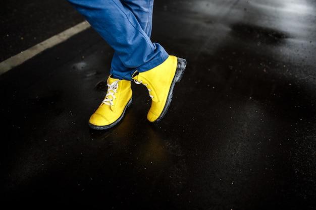 Le scarpe dell'uomo giallo sopra il fondo bagnato della via piovosa