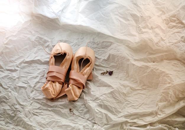 Le scarpe di balletto su sfondo, tono di luce calda, sfondo sfocato design leggero.