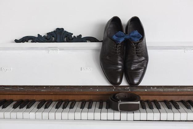 Le scarpe e la cinghia degli uomini di marrone scuro su un fondo bianco