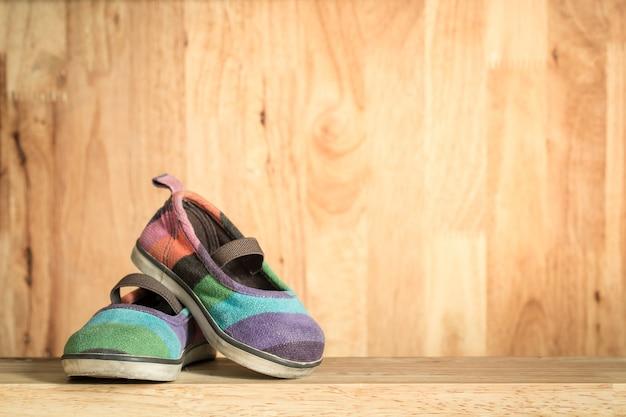 Le scarpe per bambini giacevano su un tavolo di legno.