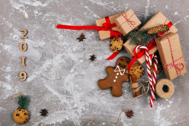 Le scatole per il regalo di colore grigio marrone con i nastri rossi stanno sul pavimento con biscotti al cioccolato, pane allo zenzero e corda prima del numero 2019