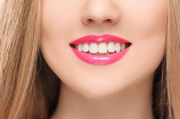 Le sensuali labbra rosse, la bocca aperta, i denti bianchi.