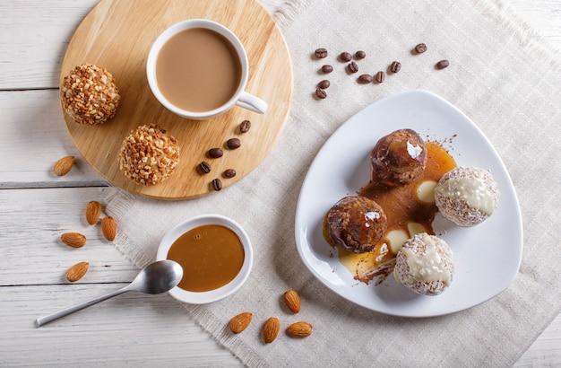 Le sfere di energia agglutina con caramello e noce di cocco del cioccolato su bianco