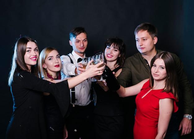Le signore e i ragazzi sorridenti in serata indossano bicchieri affollati di bevande