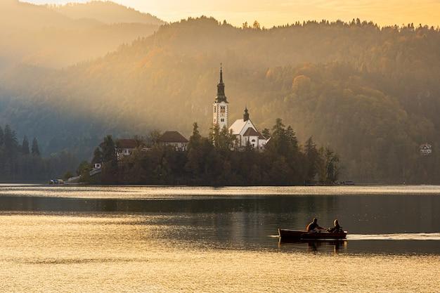 Le siluette di una coppia che galleggia su una barca vicino all'isola di bled alla bella luce del tramonto