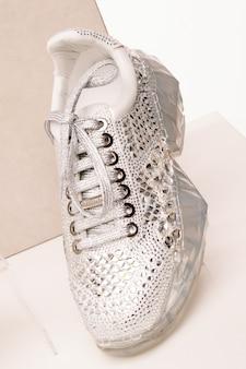 Le sneaker da donna bianche sono ricoperte di strass lucidi su uno sfondo bianco isolato in studio.